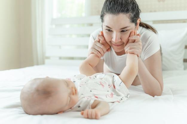 Schlafendes baby und mutter, die mit babyfüßen spielt