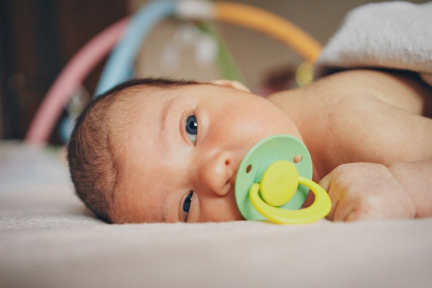 Schlafendes neugeborenes baby in einer decke mit einem schnuller im mund gewickelt. gesundheit, ivf