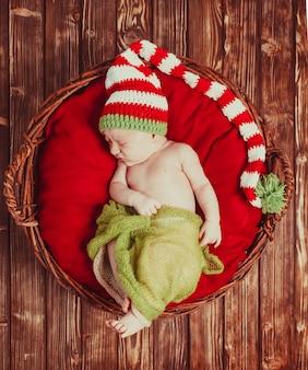 Schlafendes neugeborenes mit hut, auf roter decke im korb