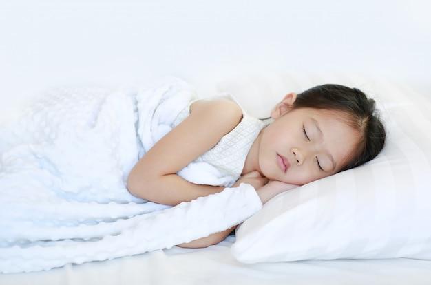 Schlafendes schönes asiatisches kindermädchen, das auf bett liegt.