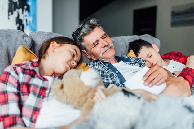 Schlafenszeit. opa mit seinem enkelkind, das auf dem bett schläft, nach märchen. familienkonzept.