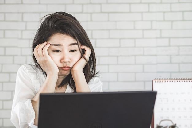 Schlaflose asiatische frau am arbeitsplatz müde und schläfrig