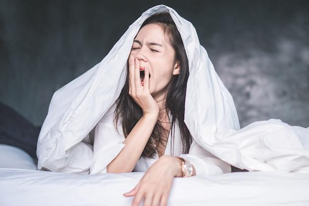 Schlaflose asiatische frau, die im bett gähnt