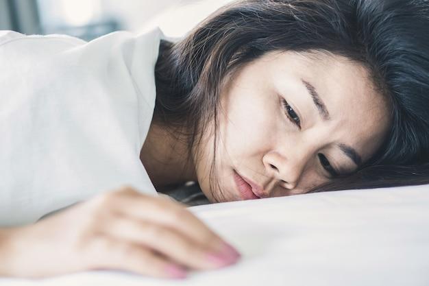 Schlaflose asiatische frau, die sich auf bett hinlegt