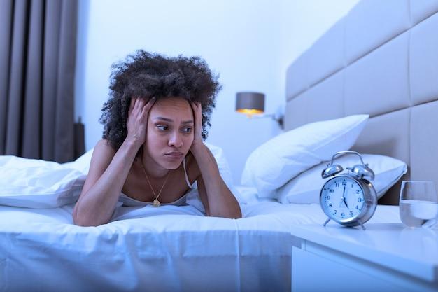 Schlaflose und verzweifelte frau, die nachts wach ist und nicht schlafen kann. sie fühlt sich frustriert und besorgt, wenn sie auf die uhr schaut, die unter schlaflosigkeit im konzept der schlafstörung leidet.