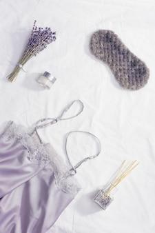 Schlafmaske, seidenpyjama, aromabalsam, trockene lavendelblüten auf weißer bettwäsche.
