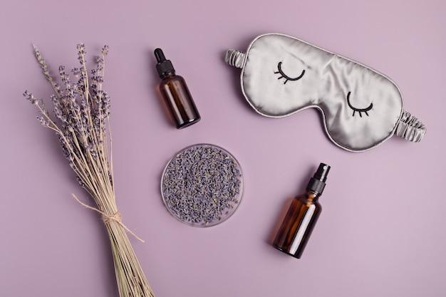 Schlafmaske und ätherisches lavendelöl auf violettem hintergrund. natürliche behandlung von schlaflosigkeit, entspannung, anti-stress, schlafqualitätskonzept. flache lage, ansicht von oben
