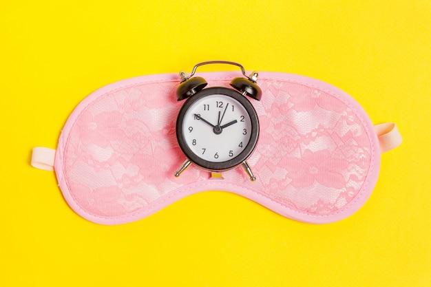 Schlafmaske und wecker auf gelbem grund