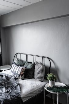 Schlafzimmer ecke mit künstlichen pflanzen in weißem keramikmarmortopf auf beistelltisch im modernen skandinavischen stil