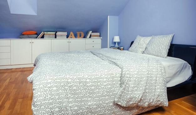 Schlafzimmer im dachgeschoss mit doppelbett und kommode mit büchern