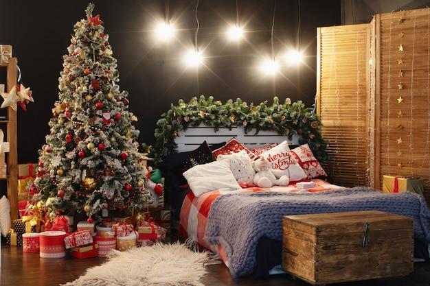 Schlafzimmer interieur in dunkler dekoration für weihnachten dekoriert. das bett mit dunkelblauem leinen und vielen kissen ist mit einer wolldecke aus hyper large schafgarn bedeckt