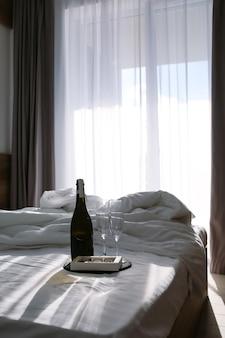 Schlafzimmer mit ausgebreitetem bett weiße bettwäsche auf dem bett mit champagner und gläsern sommer der sonnenstrahl