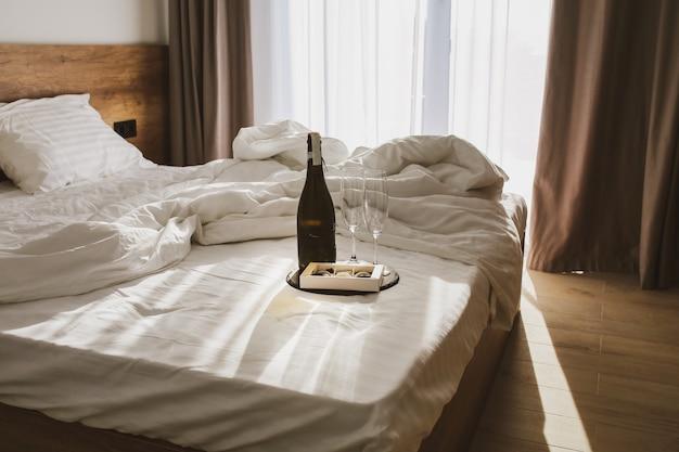 Schlafzimmer mit ausgebreitetem bett weiße bettwäsche auf dem bett mit sekt und gläsern sommer die sonnenstrahlen fallen auf das bett morgen im schlafzimmer mit sekt und süßigkeiten bett mit sekt und gläsern