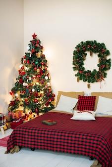 Schlafzimmer mit einem bett und einem weihnachtsbaum in roten und hellen farben.