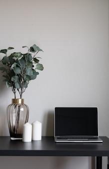 Schlafzimmerarbeitsecke verziert mit weißen kerzen des laptops und künstlicher pflanze in der glasvase auf holzarbeitstisch mit beige gemaltem wandhintergrund
