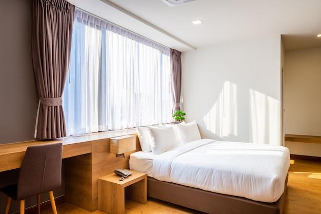 Schlafzimmerinnenraum mit dekoration des betts und der hellen lampe