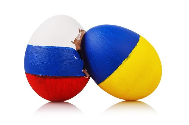 Schlag zur orthodoxie zwei ostereier gemalt in der farbe der flaggen von russland und der ukraine isoliert auf einer weißen oberfläche