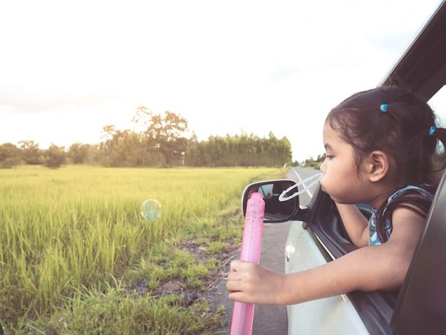 Schlagblase des netten asiatischen mädchens des kleinen kindes aus autofenster heraus und spaß haben, mit dem auto zu reisen