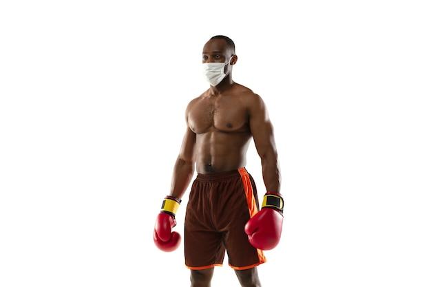Schlagen sie das virus ab. afroamerikanischer boxer in schutzmaske, handschuhen.