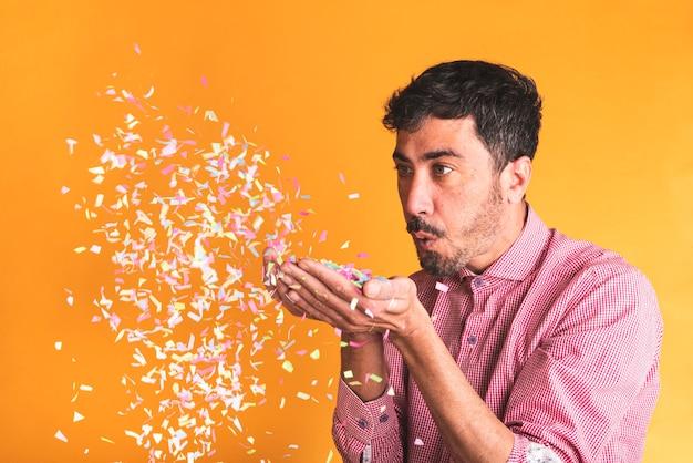 Schlagkonfettis des jungen mannes auf orange hintergrund