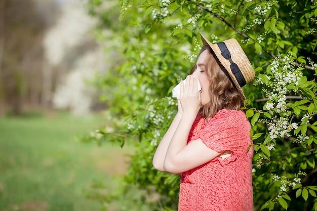 Schlagnase des jungen mädchens und niesen im gewebe vor blühendem baum. saisonale allergene bei menschen. schöne frau hat rhinitis.