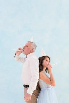 Schlagparteigebläse des kleinen mädchens mit ihrem großvater zum zeitpunkt der feier