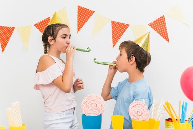 Schlagpartyhorn des jungen und des mädchens während der geburtstagsfeier
