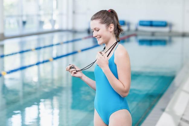 Schlagpfeife des hübschen trainers und betrachten der stoppuhr am pool