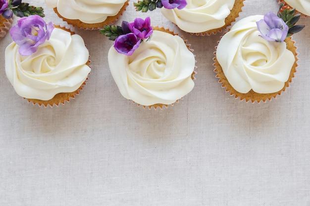 Schlagsahne, die vanillekleine kuchen mit purpurroten essbaren blumen bereift