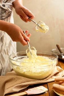 Schlagsahne-mascarpone-käse-doppelcreme für kuchen, weibliche hand. schritt für schritt rezept.