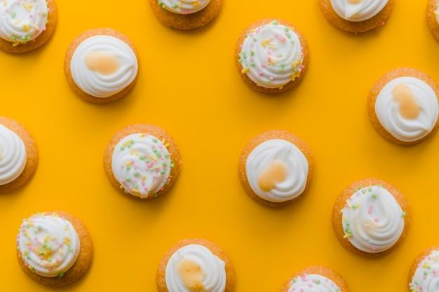 Schlagsahne über kleinem kuchen auf einem gelben hintergrund
