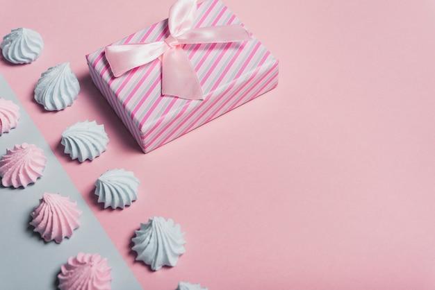 Schlagsahne und eingewickelte geschenkbox auf farbigem hintergrund