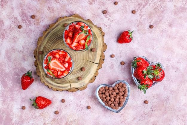 Schlagsahne und erdbeer-kleinigkeit mit honig und müsli.
