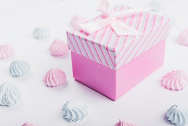 Schlagsahne und geschenkbox mit band auf weißem hintergrund