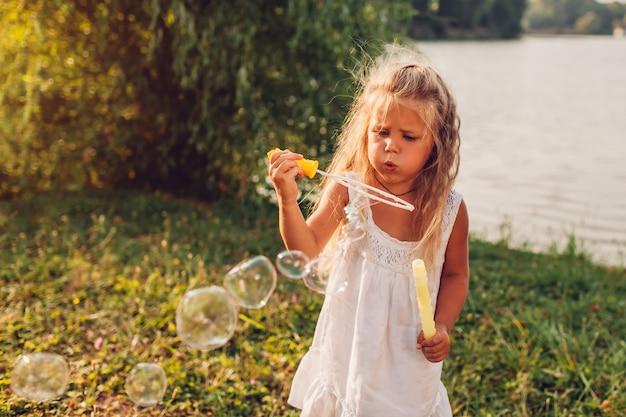 Schlagseifenblasen des kleinen mädchens im sommerpark, spaß habend