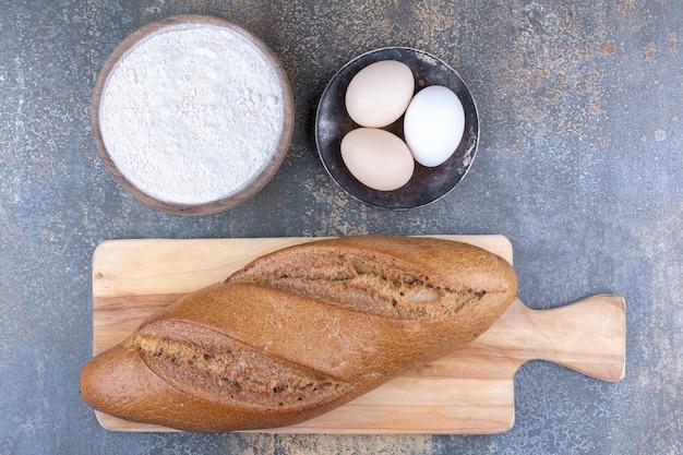 Schlagstockbrot auf einer brettmehlschale und eier auf marmoroberfläche