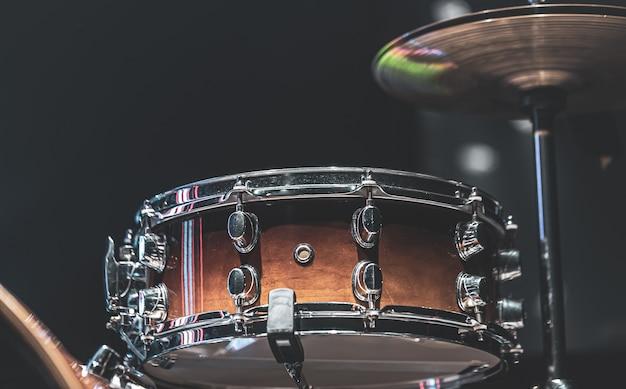 Schlagzeug in einem dunklen raum mit schöner beleuchtung, kleine trommel, becken.