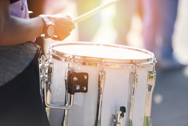 Schlagzeuger bei einer parade mit weißem trommeln - schlagzeug spielen während einer parade für die feierlichkeiten
