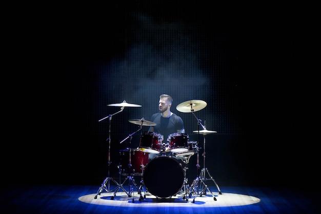 Schlagzeuger, der die trommeln mit rauche und puder spielt
