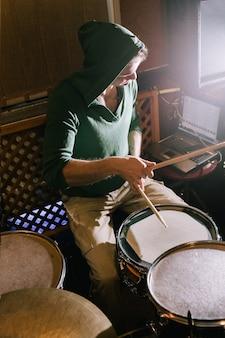 Schlagzeuger, der schlagzeug im musikstudio aufnimmt