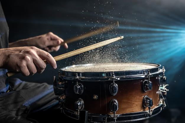 Schlagzeuger mit trommelstöcken, die snare-drum mit spritzwasser auf schwarzem hintergrund unter studiobeleuchtung schlagen.