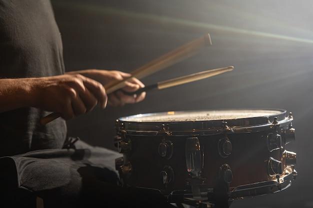 Schlagzeuger spielt percussion, snare drum auf der bühne im rampenlicht, kopierraum.