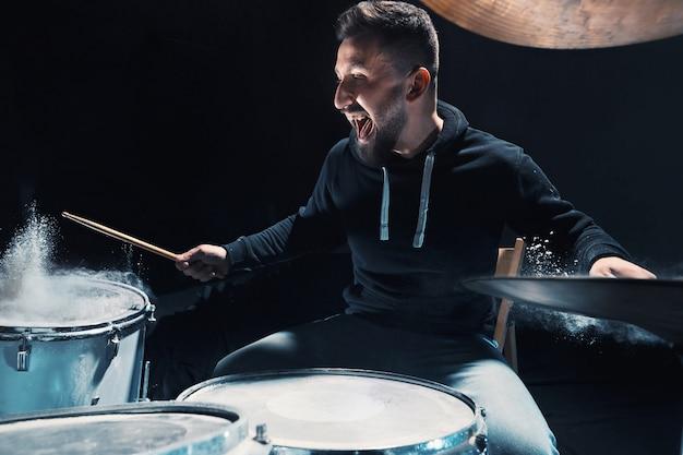 Schlagzeugprobe am schlagzeug vor dem rockkonzert. mann, der musik auf schlagzeug mit showeffekt in form von mehl aufzeichnet