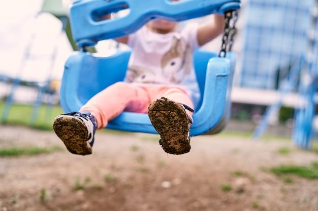 Schlammbefleckte sandalen an den füßen eines kindes auf einer schaukel nahaufnahme