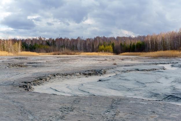 Schlammiger boden eines ausgetrockneten sees im hintergrund der landschaft im zeitigen frühjahr