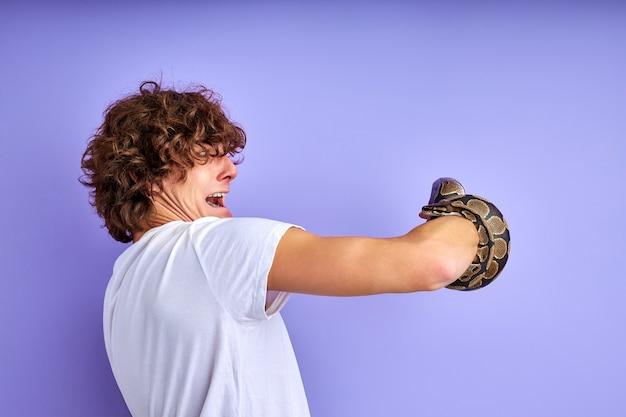 Schlange an hand gebunden, ängstlicher mann ist in schock, seitenansicht auf lockigem kerl, der arm mit schlange lokalisiert auf lila hintergrund betrachtet
