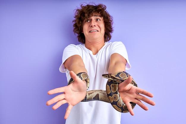 Schlangengebundene männerhände. der typ weint vor angst und überlegt, wie er sich aus den fesseln der schlange befreien kann