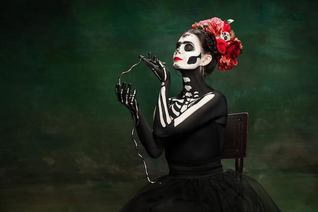 Schlangenkönigin. junges mädchen wie santa muerte saint death oder sugar skull mit hellem make-up. porträt lokalisiert auf dunkelgrünem studiohintergrund mit exemplar. feiern von halloween oder tag der toten.