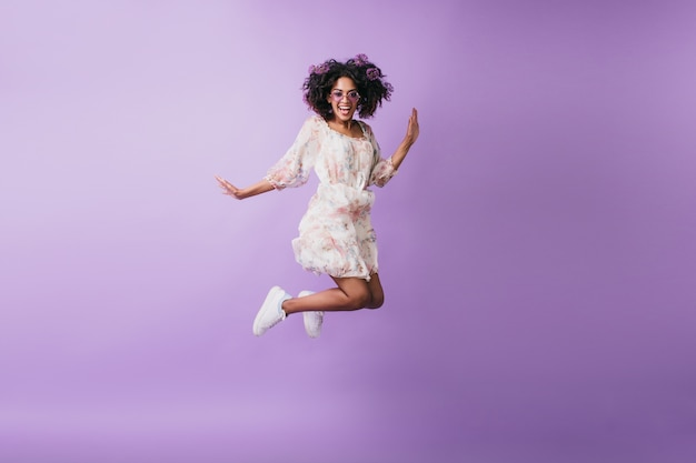 Schlanke afrikanische frau in den weißen turnschuhen, die springen und lachen. innenfoto des gut gelaunten schwarzen mädchens tanzen.