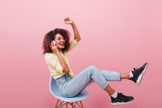 Schlanke afrikanische frau mit langen beinen, die musik hört und lacht. atemberaubendes weibliches mulattenmodell in schwarzen schuhen, die auf blauem stuhl sitzen.